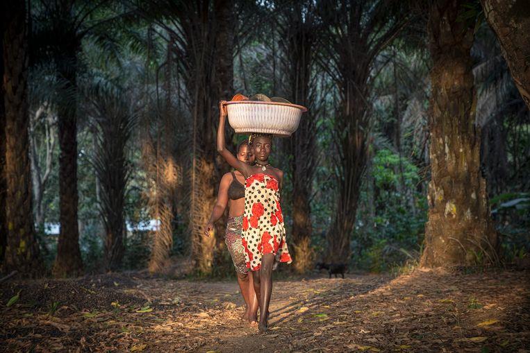 Vrouwen uit Tonka op weg naar de Ronkel-rivier om de was te doen. Beeld