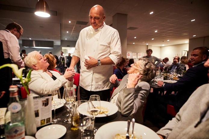 Herman den Blijker heeft zijn handen vol, niet alleen aan het maken van tv-programma's. Hier was hij bij de donateurs van Rotterdammers 4 Rotterdammers (R4R) waar hij een diner voor honderd Rotterdamse wederopbouwers verzorgde. Den Blijker maakte een praatje met enkele gasten tijdens het hoofdgerecht.