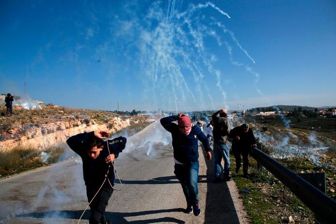Palestijnen vluchten weg voor traangasgranaten afkomstig van Israëlische soldaten na een uit de hand gelopen demonstratie in het dorp Nabi Saleh op de Westelijke Jordaanoever. Foto Abbas Momani