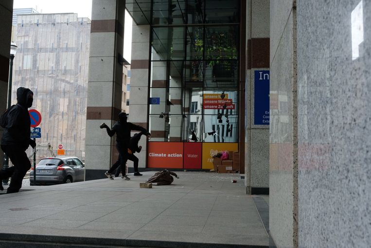 Gemaskerde relschoppers richten schade aan in de Wetstraat.