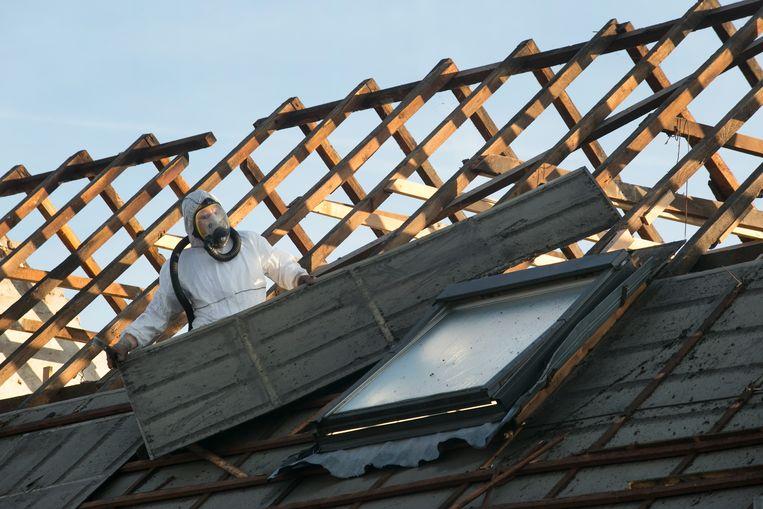 Het verwijderen van asbestplaten van een dak. Beeld ter illustratie.