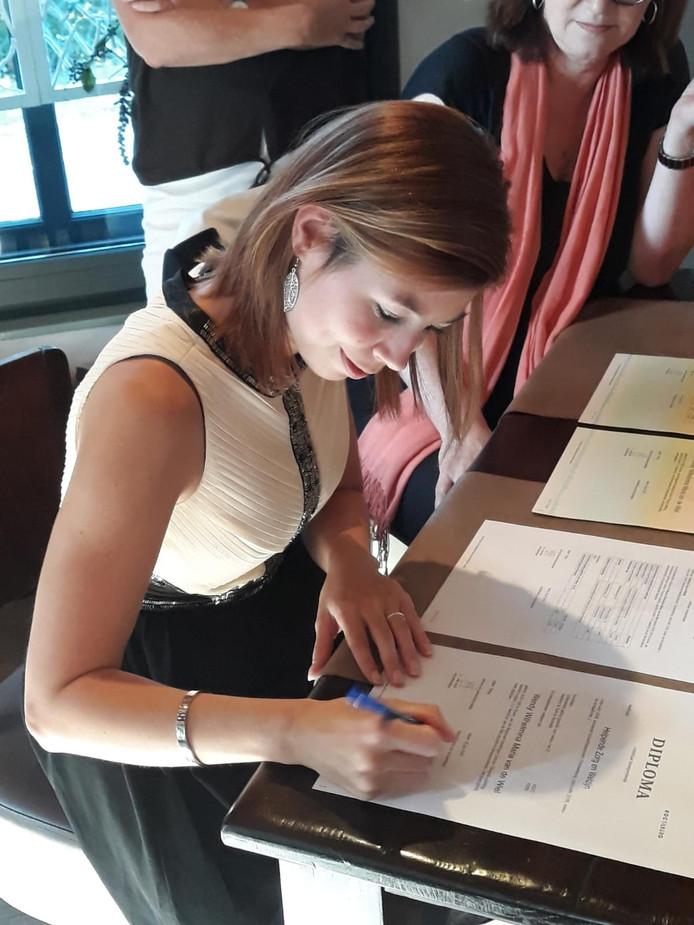Wendy van de Wiel zet haar handtekening onder haar mbo-diploma.