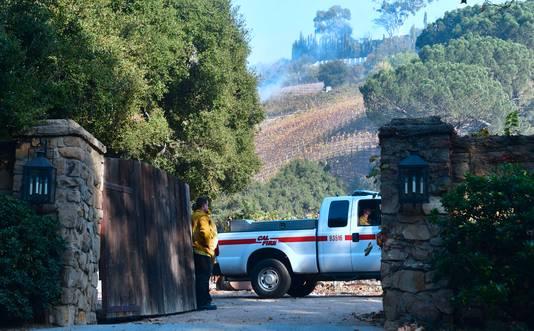 Brandweermannen staan bij de ingang van de wijngaard Moraga Estate in de wijk Bel Air.