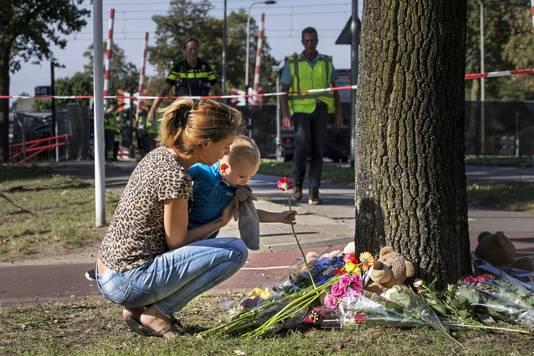 Belangstellenden leggen bloemen neer bij een spoorwegovergang, na een ongeluk met een bakfiets (Stint) en een trein waarbij meerdere doden en zwaargewonden zijn gevallen.