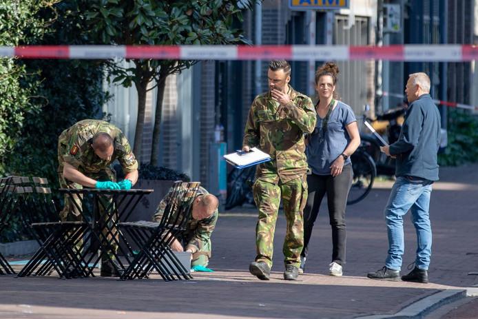 Medewerkers van de Explosieve Opruimingsdienst doen onderzoek in de Spuistraat. In die Amsterdamse straat werd in korte tijd twee keer een handgranaat gevonden.