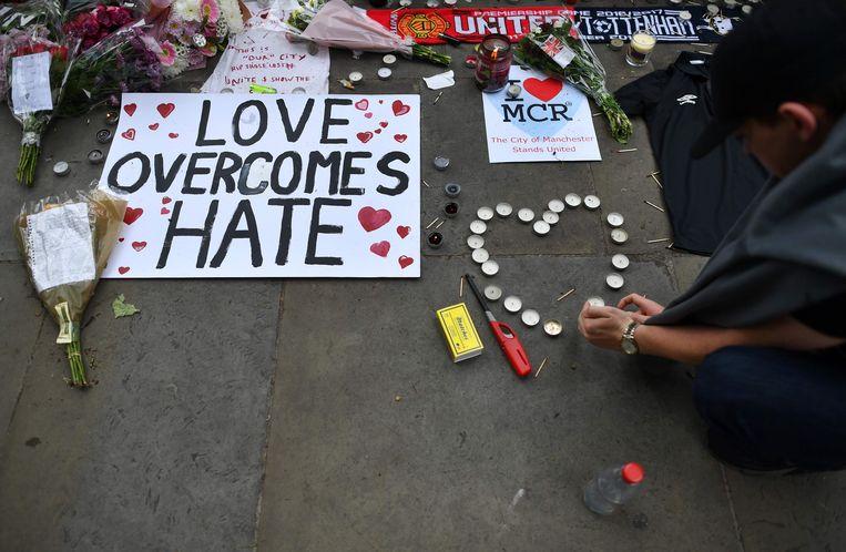 In Manchester steekt een man kaarsjes aan ter nagedachtenis aan de slachtoffers van de aanslag. Beeld AFP