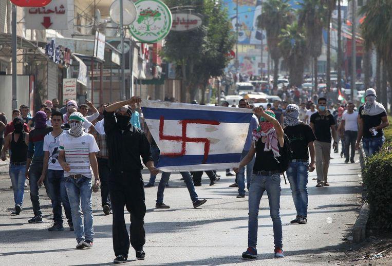 Gemaskerde Palestijnen lopen in Hebron over straat met een geïmproviseerde Israëlische vlag, met daarop een swastika in plaats van de Davidster. Beeld afp