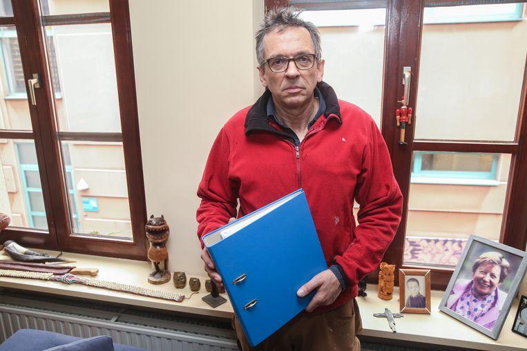 Jürgen Gielen met zijn dossier in zijn woonkamer. Op de achtergrond de achterzijde van het MIAT, waar het geluid vandaan komt.