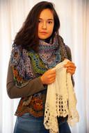 Miriam Jaffari houdt een origineel omslagdoekje vast en heeft een moderne variant omgeslagen