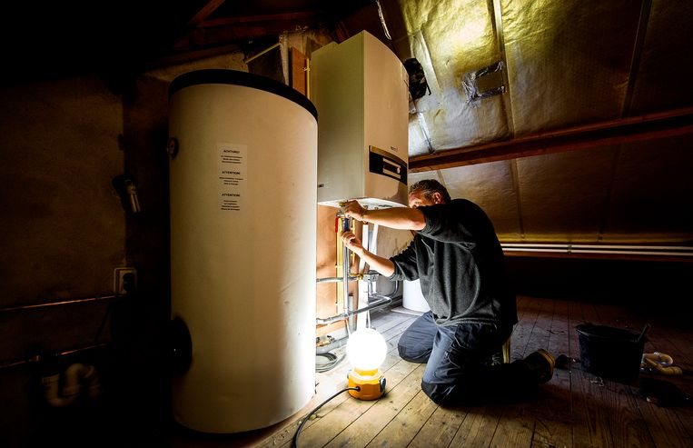Een installateur is bezig met de plaatsing van een warmtepomp bij een traditionele verwarmingsketel. Beeld ANP