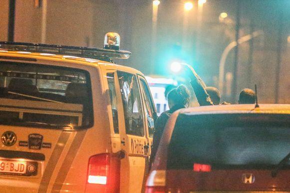 Een man wordt door de politie meegenomen.