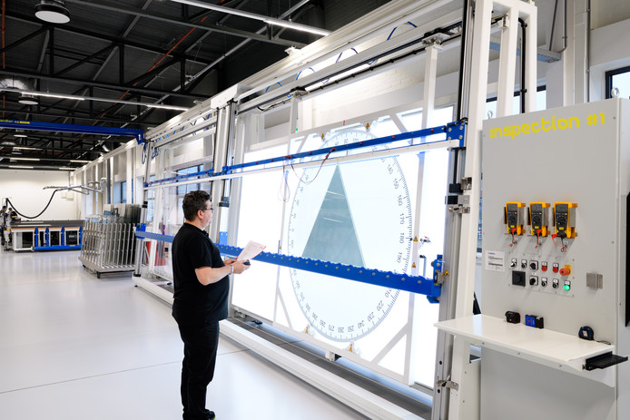 Aan het eind van de productielijn worden de glaspanelen nauwkeurig gecontroleerd.
