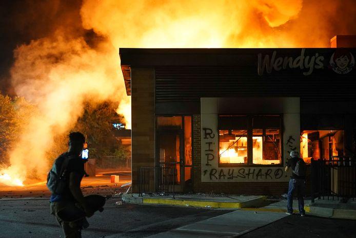 Demonstranten bij het brandende Wendy's restaurant, waar dit weekend een zwarte man werd doodgeschoten door de politie.