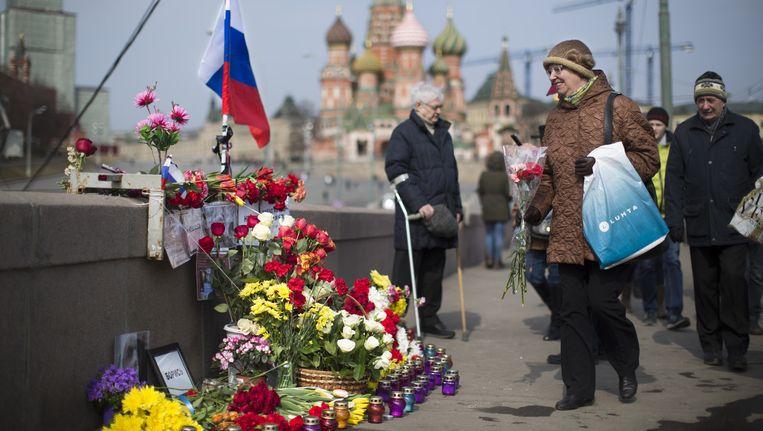 Een vrouw legt op 27 maart, een maand na de aanslag, bloemen op de plek waar Nemtsov werd gedood. Beeld AP