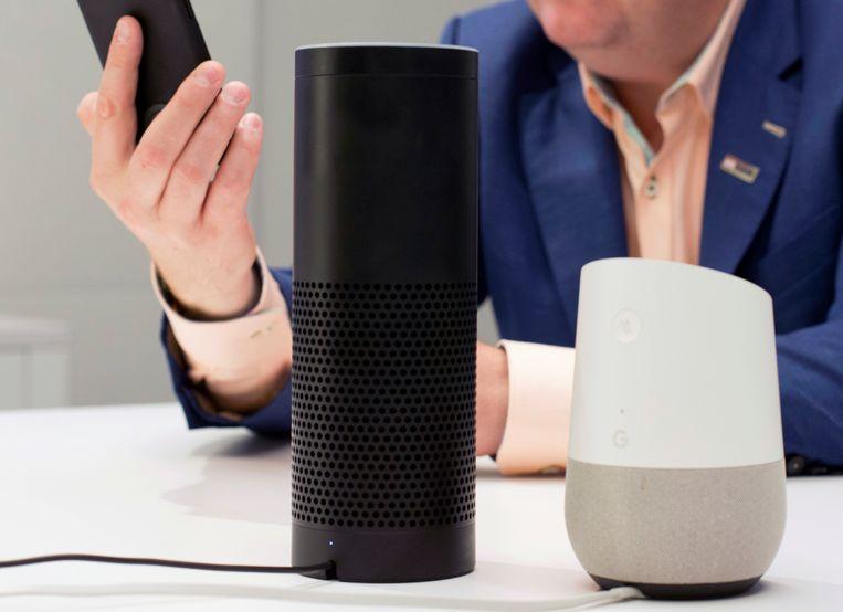 De Amazon Echo (links) en Google Home (rechts). Beide zijn slimme speakers, die reageren op gesproken commando's. Bijvoorbeeld om online zoekopdrachten uit te voeren, of om apparaten in huis te bedienen. Beeld AP