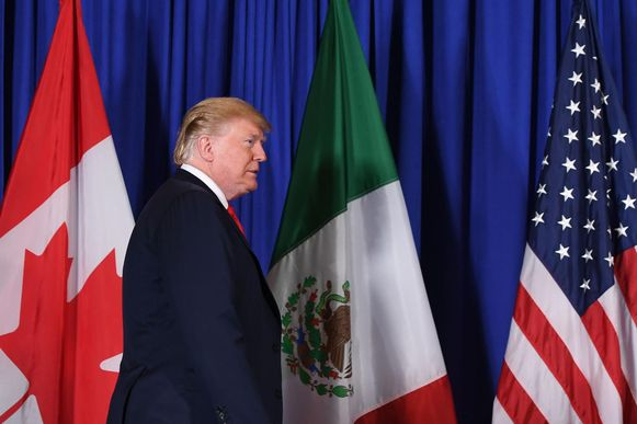 De Amerikaanse president Donald Trump loopt voor de Canadese, Mexicaanse en Amerikaanse vlaggen langs.