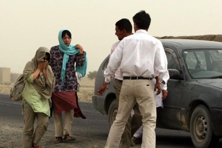 De twee vrijgelaten Zuid-Koreaanse vrouwen worden in de Afghaanse provincie Ghazni opgevangen door twee medewerkers van het Rode Kruis. De Taliban hebben maandag de twee zieke Zuid-Koreaanse gijzelaars laten gaan. (AP) Beeld