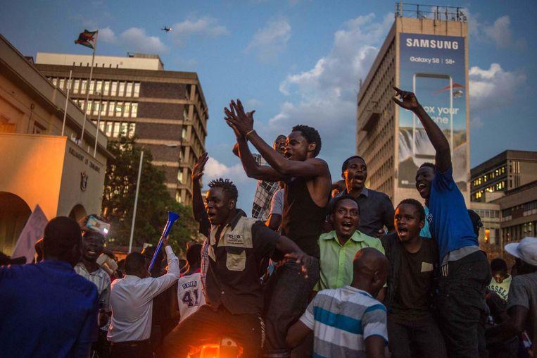 Zimbabwanen vieren feest voor het parlementsgebouw in Harare. Beeld afp