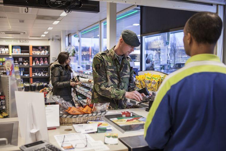 Militair in uniform rekent af bij een tankstation. Beeld null