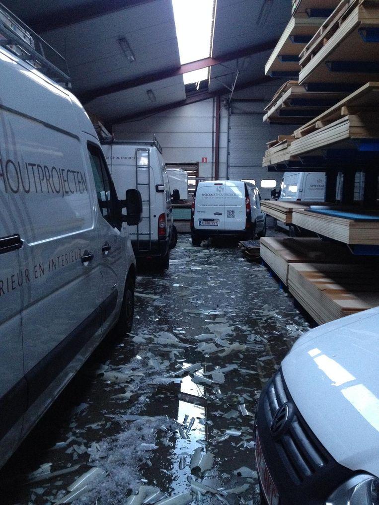 Spectaculaire hagelschade bij schrijnwerkerij Speeckaert. Hagel sloeg de lichtkoepel in het dak kapot, waardoor de wagens beschadigd raakten.