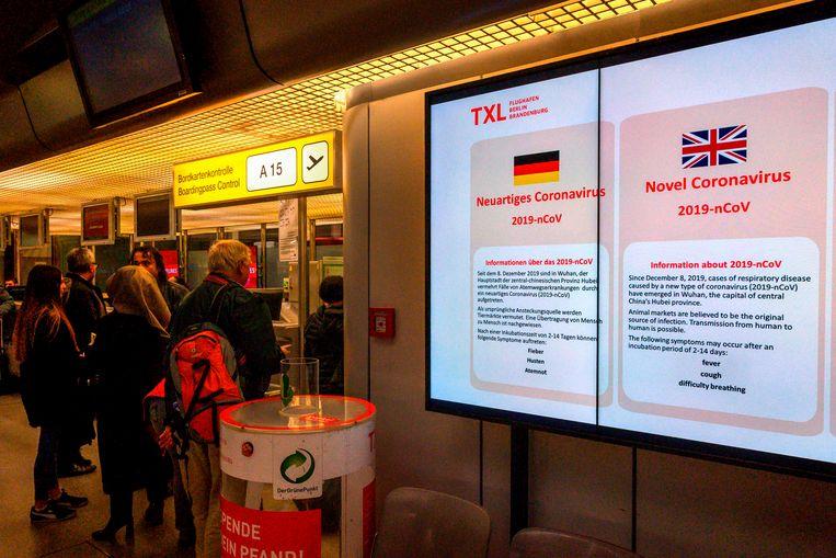 Informatie over het coronavirus op de luchthaven van Berlijn.  Beeld AFP