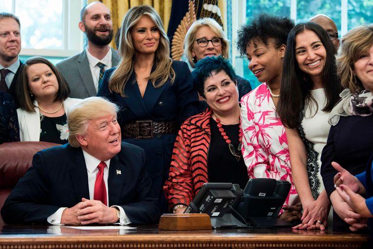 Trump in zijn kantoor met een groep van vijftig onderwijzers om zich heen. Beeld AFP
