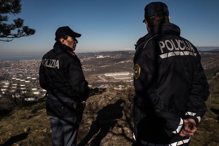 Een Italiaanse en een Sloveense grenswacht patrouilleren, met uitzicht op Triëst, de Italiaanse stad die migranten hopen te bereiken. Beeld Zolin Nicola