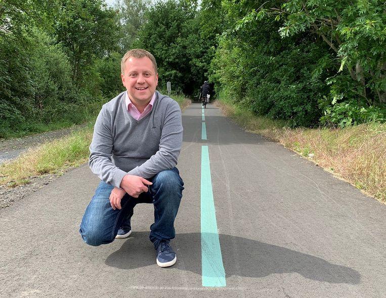 Karel Noppe (Open Vld) bij het fietspad tussen Lokeren en Eksaarde, waar al zo'n fluorescerende, appelblauwzeegroene strook wordt gebruikt als alternatief voor klassieke verlichting.