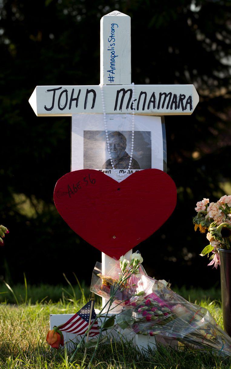 Een kruis met een foto van John McNamara in de tuin van The Capital.