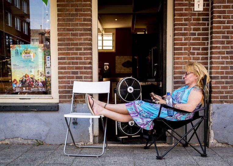 Een vrouw zoekt verkoeling voor haar winkel in Amsterdam tijdens een bloedhete julidag in 2018. Beeld ANP