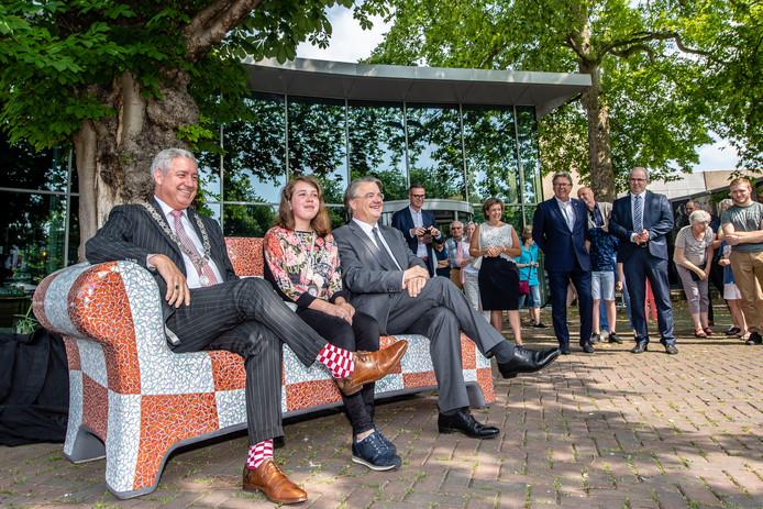 Burgemeester Jacques Niederer (l.) eerder dit jaar op het net geplaatste Roosendaalse benkske op het Tongeloplein. Rechts van hem Nikki Tjassens Keiser uit Bosschenhoofd ('Gast van de Burgemeester') en de Brabantse commissaris van de Koning Wim van de Donk.