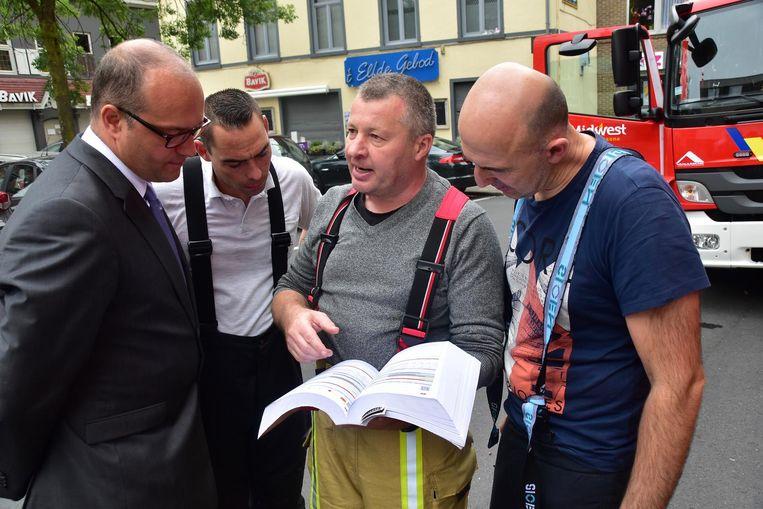 Uitvaartondernemer en brandweerman Stefaan Snoeck (links) bespreekt met zijn collega's het gevaar in de kerk.