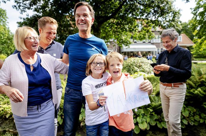 Minister president Mark Rutte gaat snel op de foto met twee Oisterwijkse jongetjes, Evans Mols en Morris van Geloven.