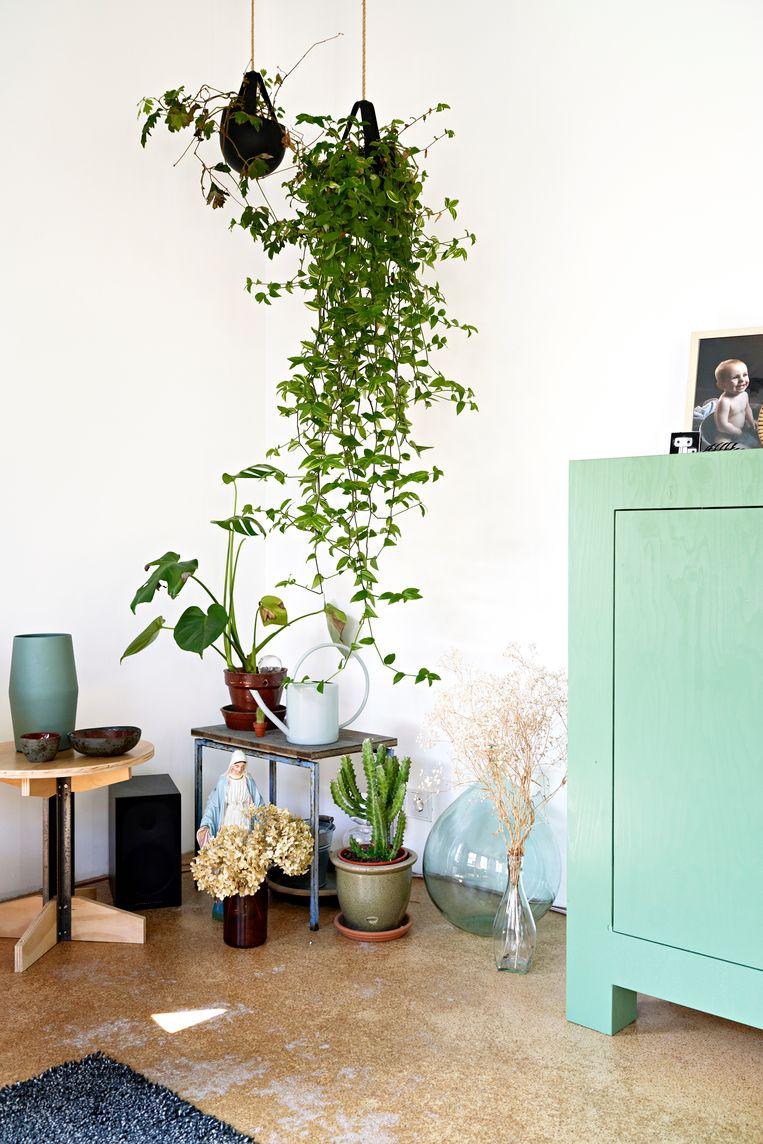 Hoekje: 'Tijdens een weekend in Arnhem zagen we hangplanten in een café, op de terugweg zijn we meteen langs het tuincentrum gereden.' Kastje en tafel zijn eigen ontwerp, de blauwe vaas komt van een Franse rommelmarkt.  Vloer: Ciske: 'Dit is magnesiet: een mengsel van houtpulp, zoutoplossing en water. Je krijgt er een soort lichtgewicht houten gietvloer mee. Normaal leg je er nog een dekvloer over, maar we vonden dit kleurenpatroon mooi. Ik heb 'm wel met epoxy behandeld.'  Beeld Jordi Huisman
