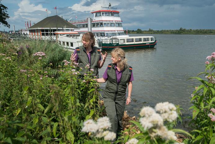 Angela Knook (l) en Eveliene Jansen van Staatsbosbeheer aan de oevers van de Amer, met op de achtergrond de toeristische rondvaartboten en de Biesbosch.
