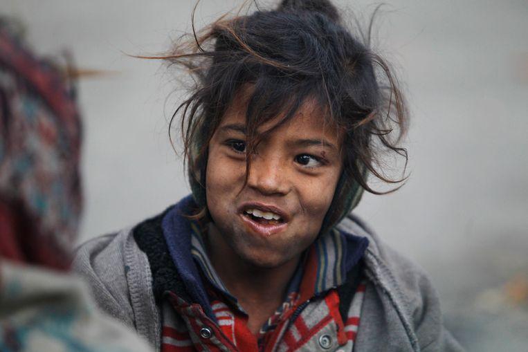 Een dakloos kind zit onder een viaduct in het Indiaase Jammu. Volgens Oxfam Novib worden vooral vrouwen en meisjes geraakt door toenemende ongelijkheid in de wereld. Beeld AP