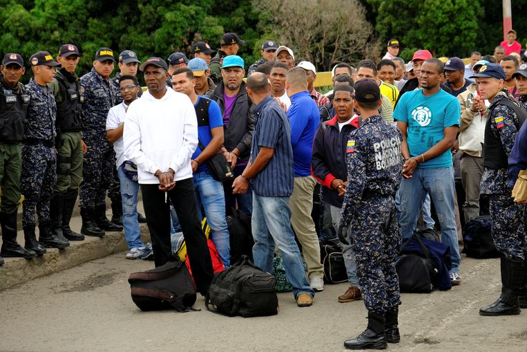 Onder begeleiding van Venezolaanse veiligheidstroepen wachten de 59 Colombianen op de Simon Bolivar-brug op het moment dat ze de oversteek kunnen maken naar hun vaderland.  Beeld REUTERS