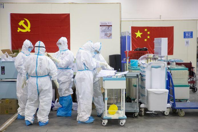 Gezondheidsmedewerkers in beschermingspak in een speciaal opgezet ziekenhuis in miljoenenstad Wuhan, in de Chinese provincie Hubei. Beeld van 17 februari.