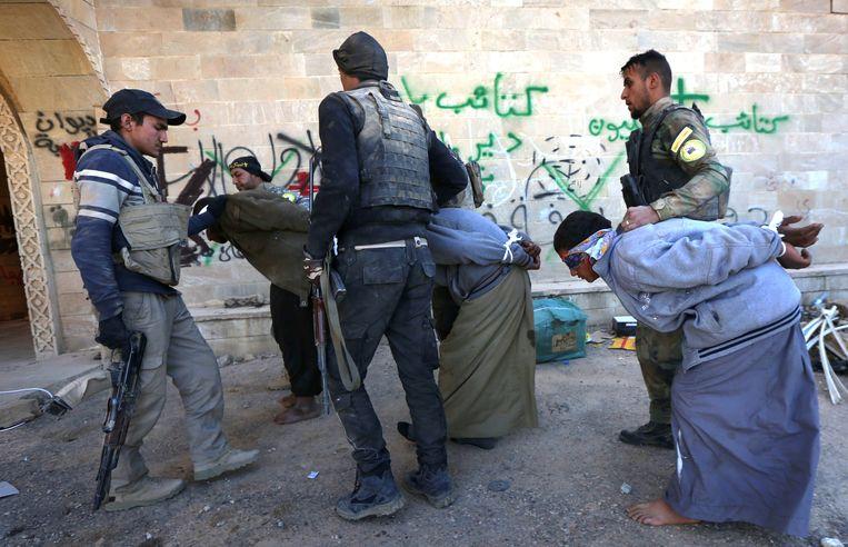 Soldaten van de christelijke Babylon-brigades houden verslagen IS-strijders vast in een klooster nabij Mosul in Irak. Beeld AFP