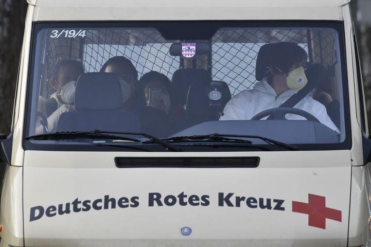 Een bus van het Duitse Rode Kruis met Duitsers die onlangs in Wuhan zijn geweest.  Beeld AFP