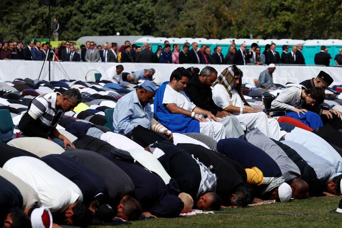 Moslims bidden buiten in Hagley Park in Christchurch bij de getroffen Al-Noor moskee, een week na de dodelijke aanslagen in de stad. Ze worden beschermd door een mensenketting die om hen heen staat.