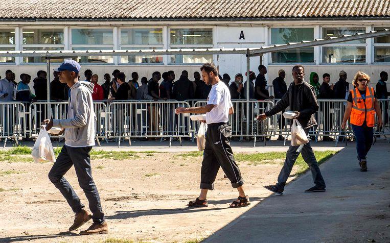 Asielzoekers staan in de rij voor de voedselbedeling door 'Vie Active' in het kamp in Calais.