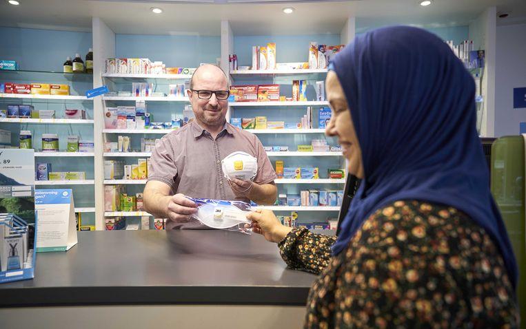 Een mevrouw haalt een mondkapje bij een apotheek in Den Haag.  Beeld Phil Nijhuis / ANP