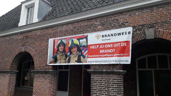 Spandoek op brandweerkazerne van Sluis met een oproep om vrijwilliger te worden.