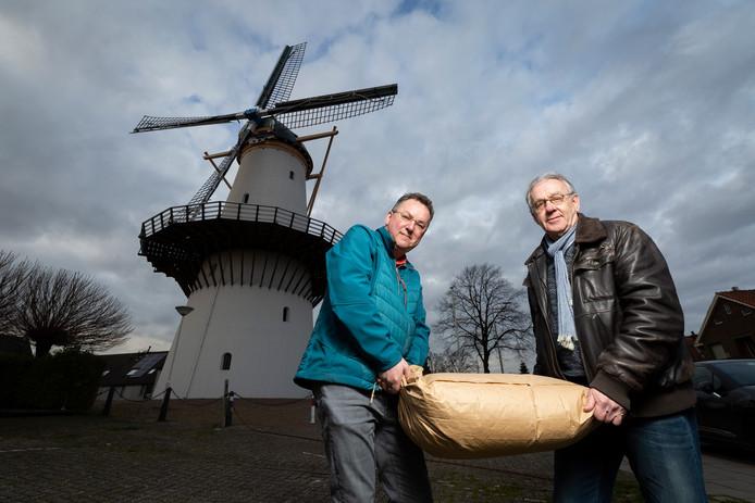 Cor Groen en Jacques Boonekamp van Stichting Molen De Hoop met een zak meel.