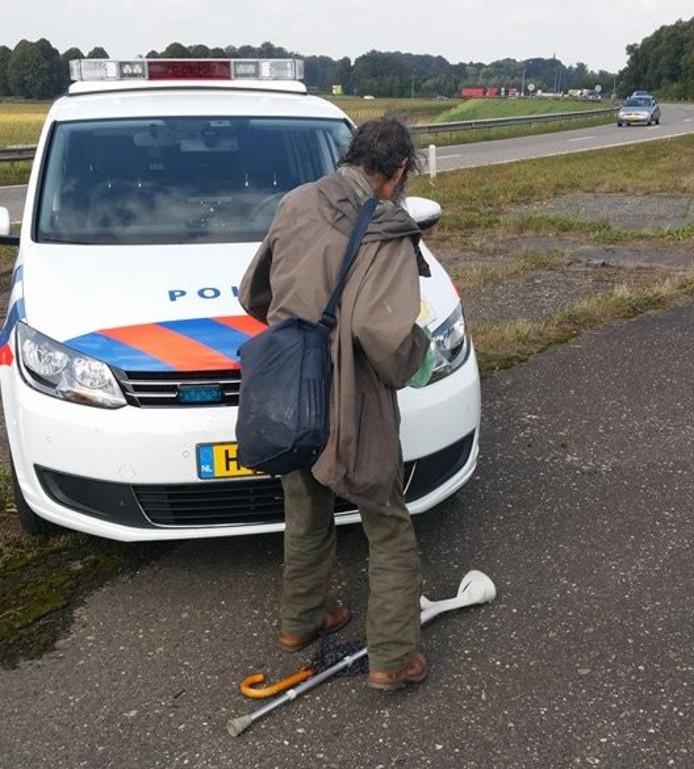 De bejaarde man voor de politiewagen.