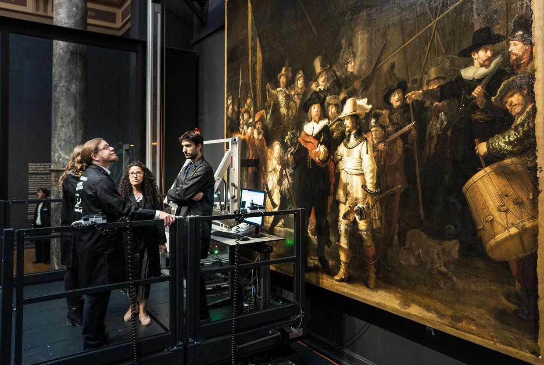 Restaurateurs werken achter een glazen wand aan de restauratie van de Nachtwacht. Het wereldberoemde meesterwerk uit 1642 van Rembrandt van Rijn is voor het laatst onder handen genomen in 1976.