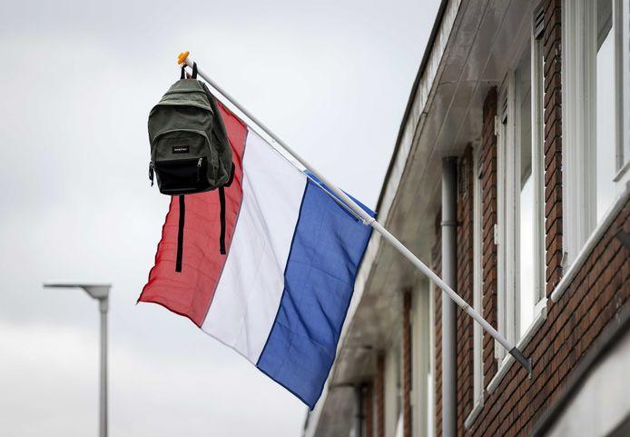 Een vlag met een schooltas hangt aan een woning.