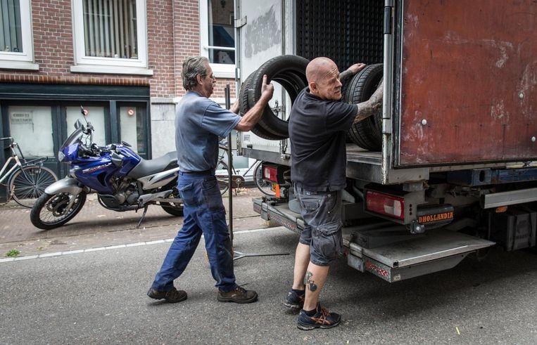 Een opkoper haalt een partij banden op bij John (met blauw shirt) en Peter Lucke. De garage moet schoon en leeg worden opgeleverd. Beeld Dingena Mol
