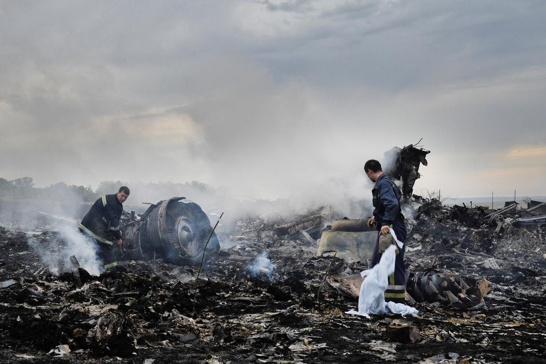 Brandweerlieden zoeken tussen de restanten van vlucht MH17.